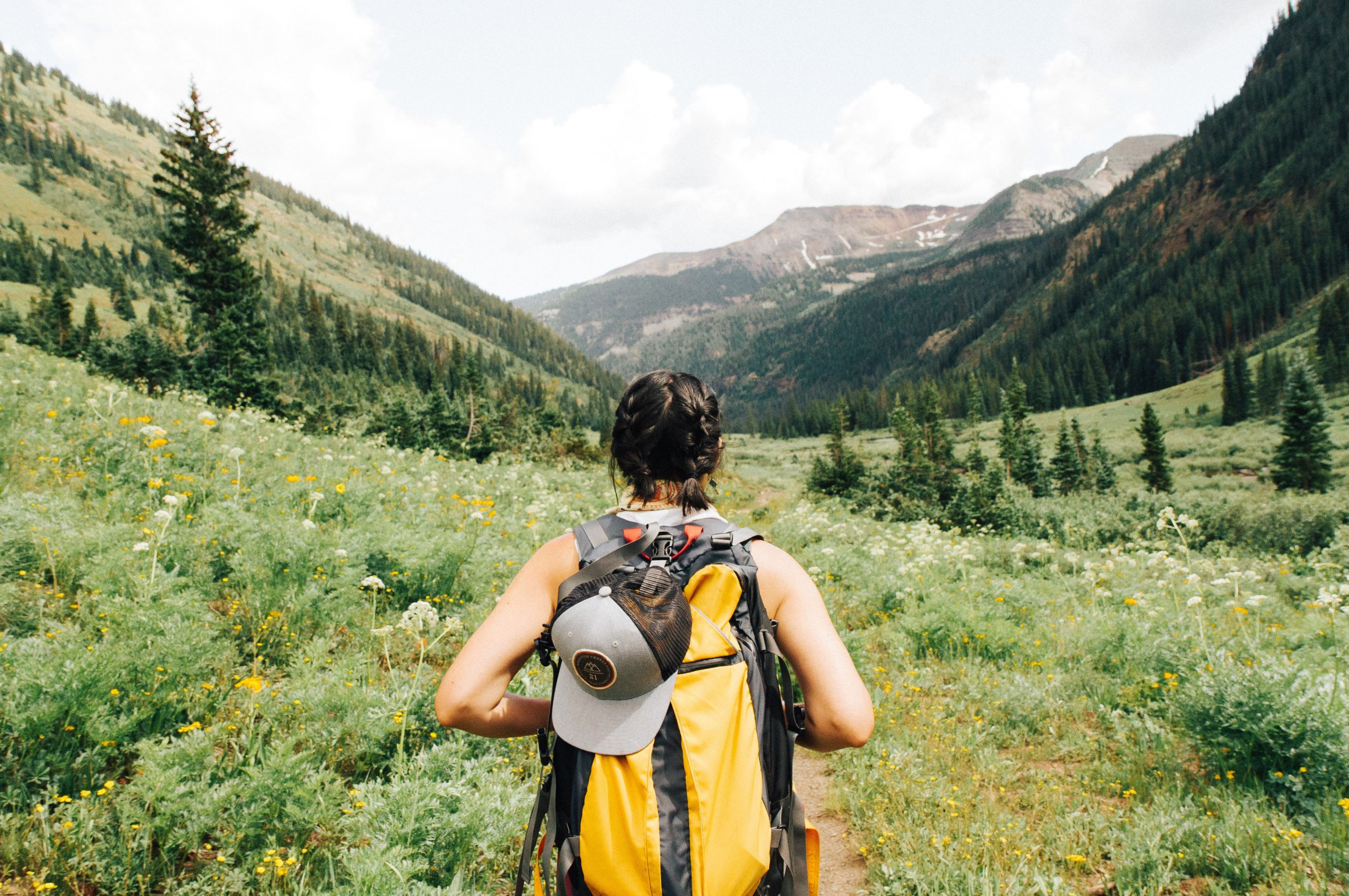 A person with a yellow backpack going on an adventure in lush green mountains