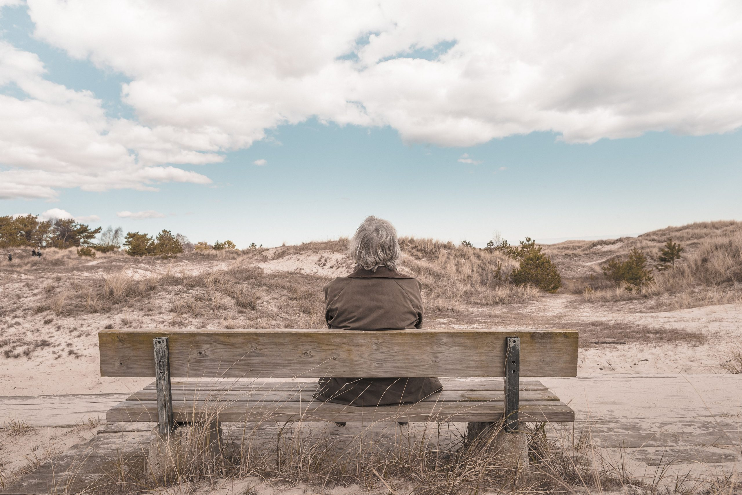 A gray haired person sitting on a bench in a desert taking a break to reignite your creative spark